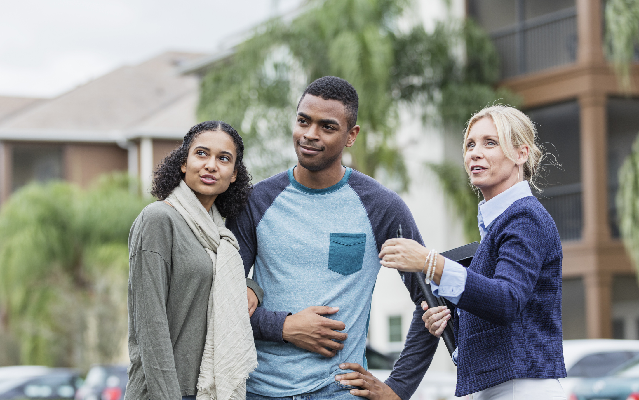 Stock photo of a couple and a real estate agent standing outside looking toward a home