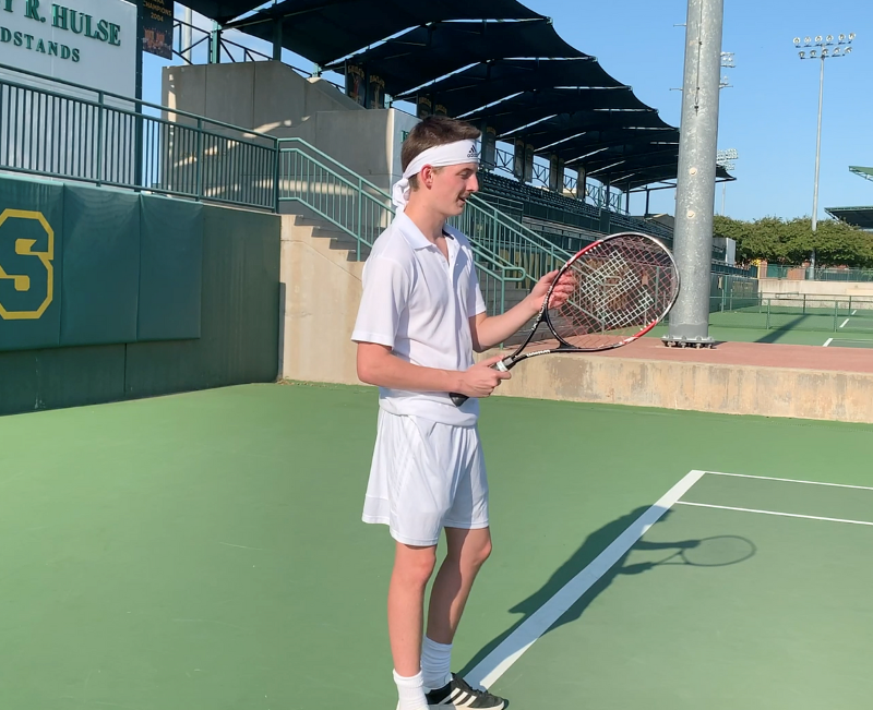 A cast member warms up on a tennis court