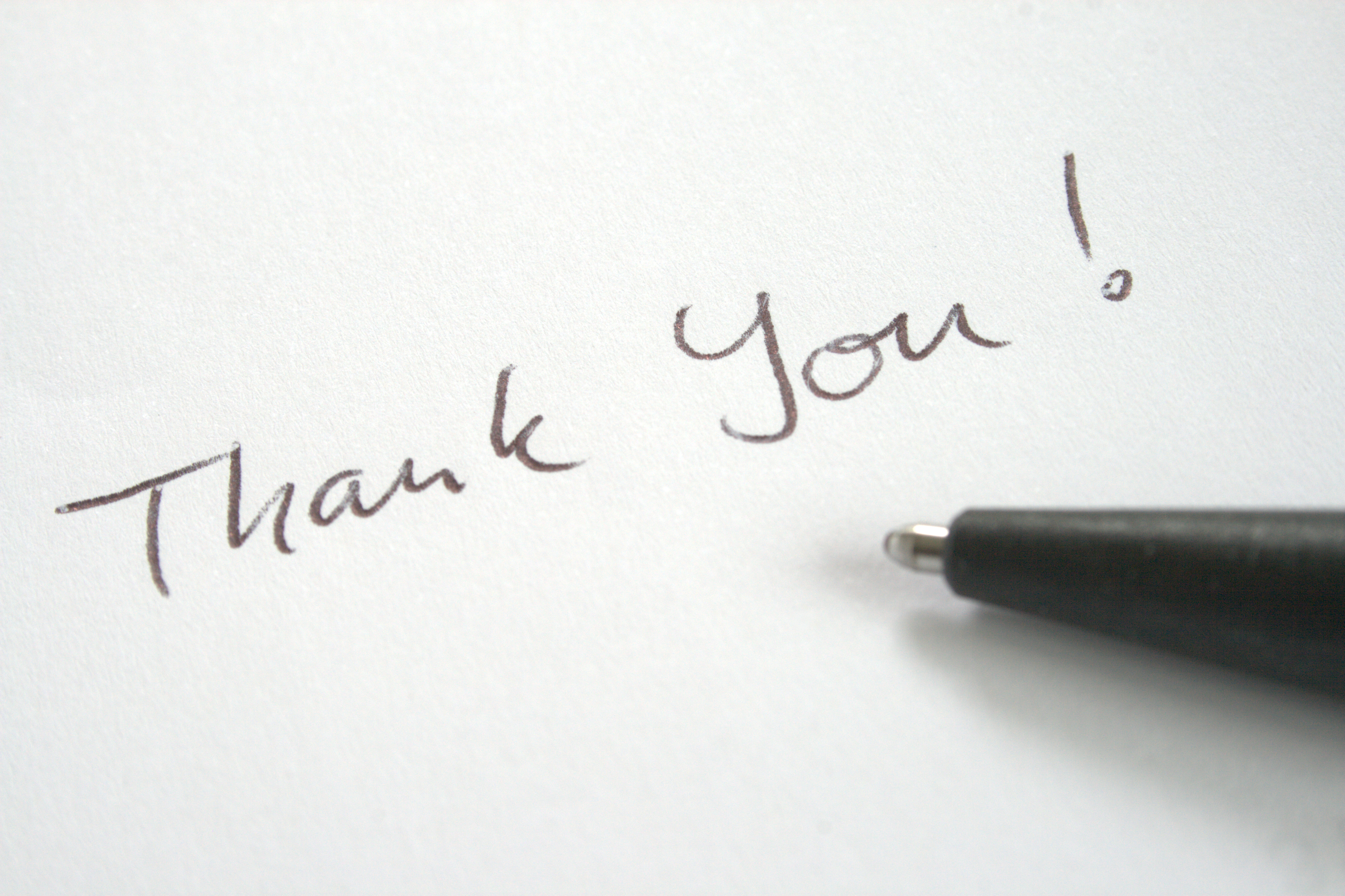 Stock photo of pen writing the words thank you on a piece of paper