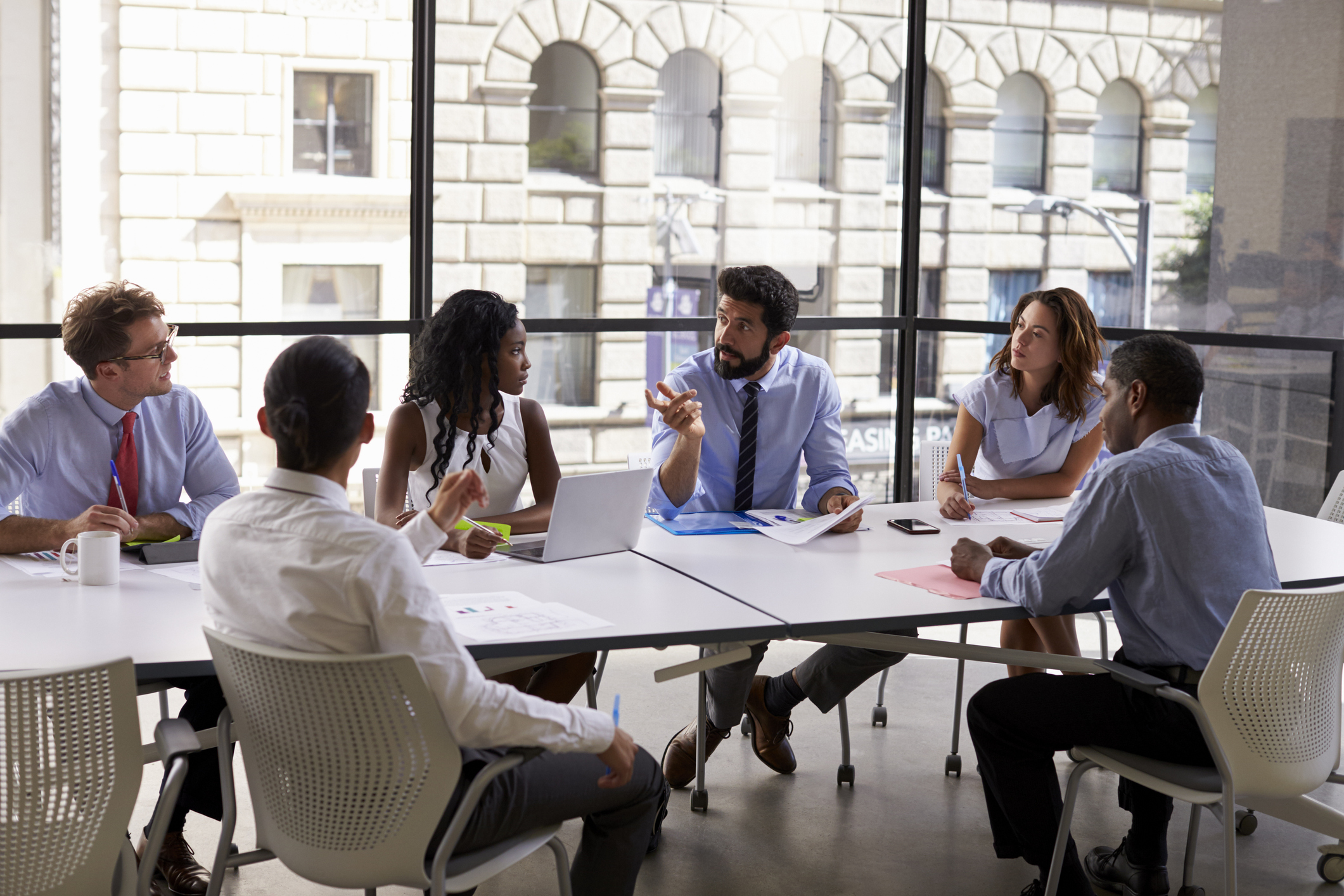 Stock photo of group of business professionals sitting around conference room table at a meeting with their supervisor