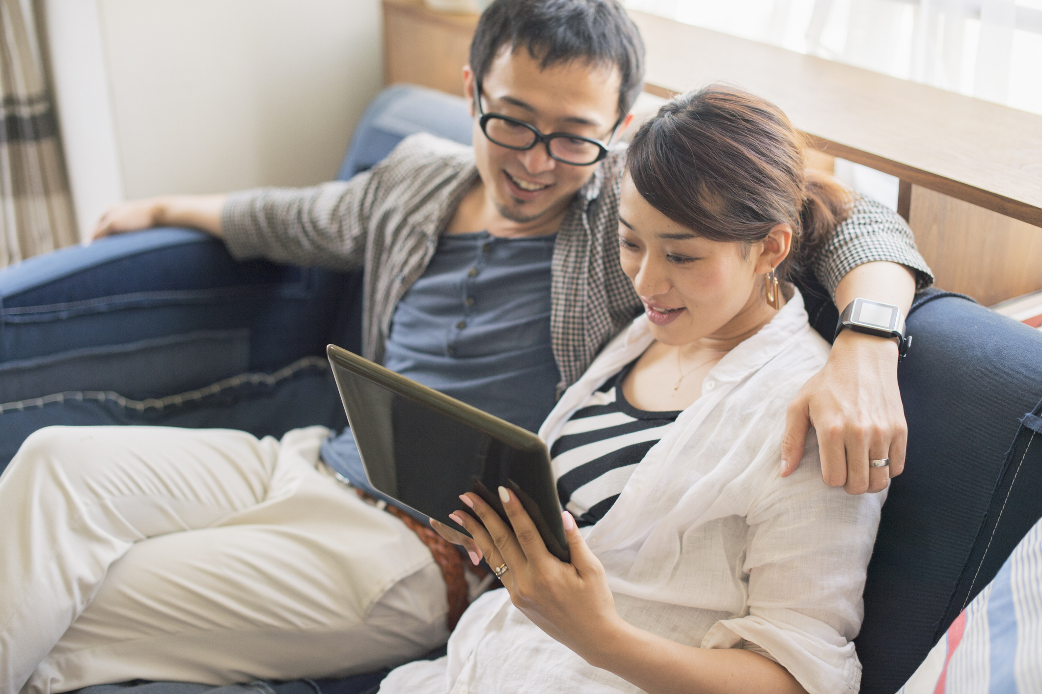 Stock photo of man and woman looking at a tablet and smiling