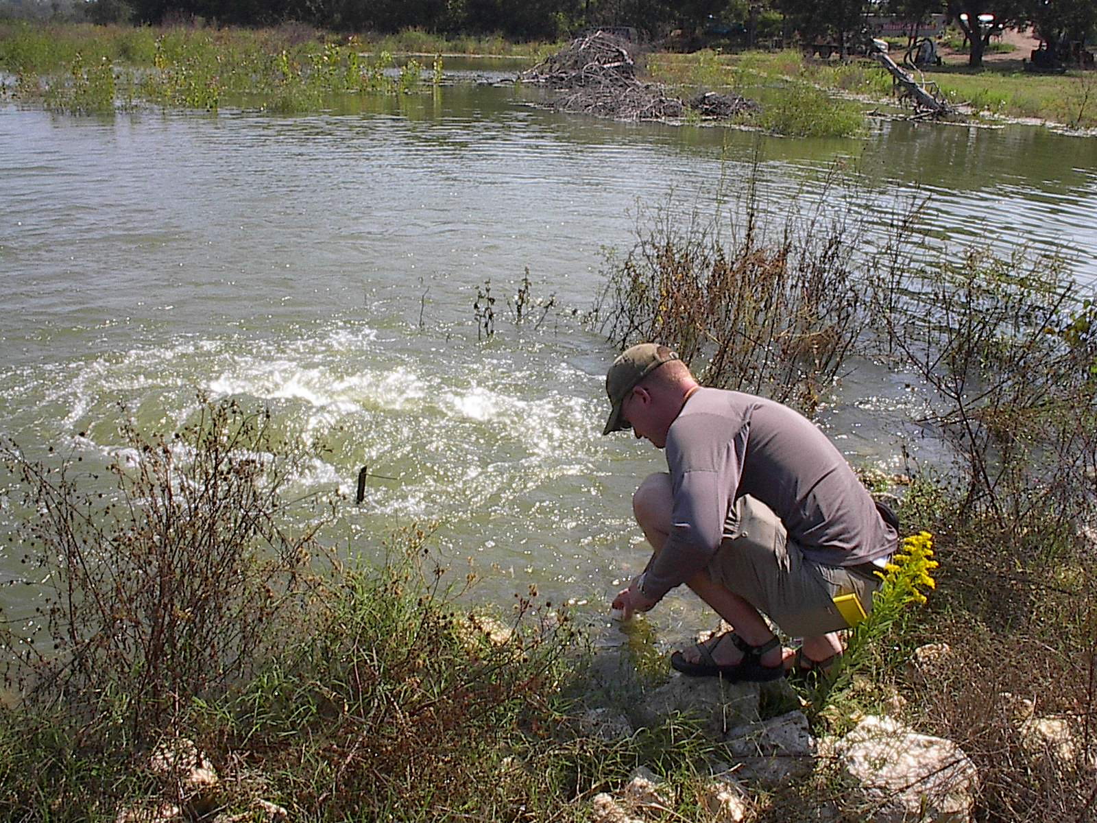 Jeremy Andrews taking a water sample from a Waco infill pipe.